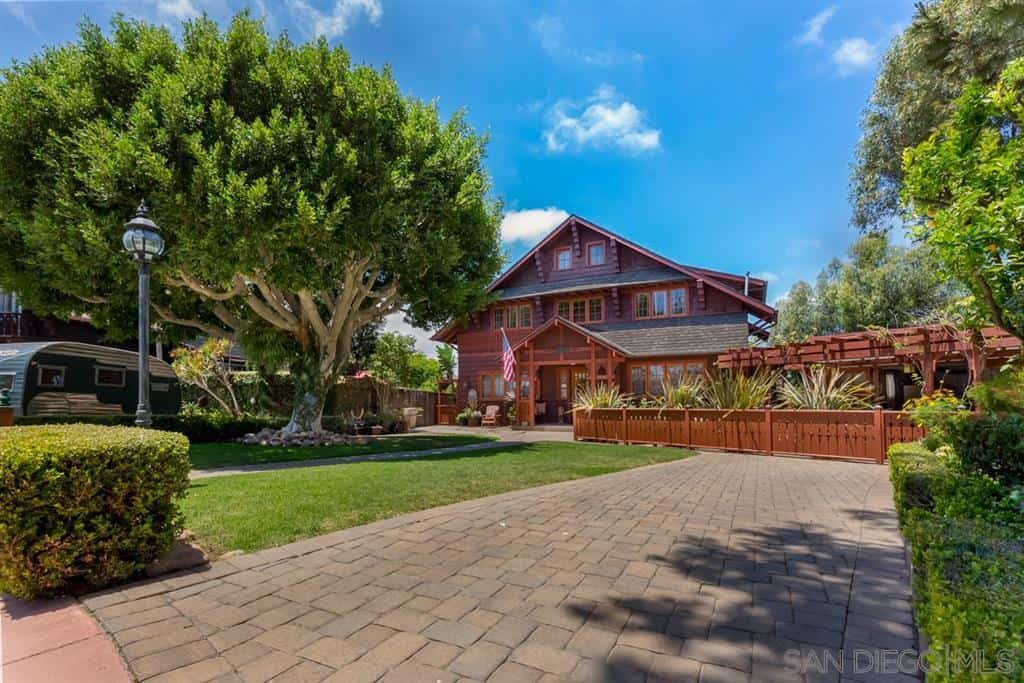 There is a wide and spacious front lawn to this Craftsman-Style house with a huge tree that provides a nice foreground to the redwood hues of the house. The wooden trellis on the side of the house also has the same redwood finish contrasted with various plants.