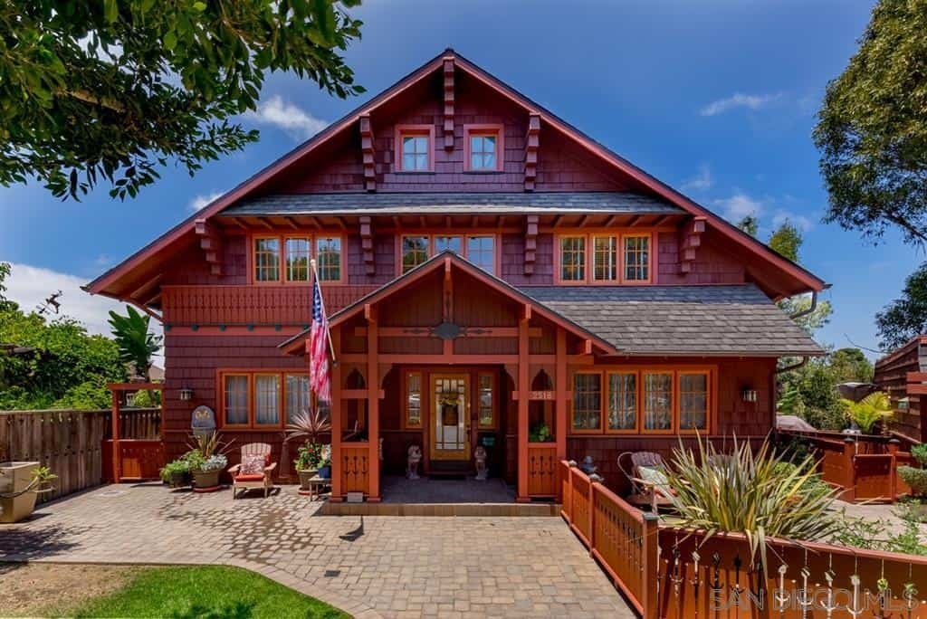 This three-story Craftsman-Style house is dominated by varying hues of redwood from its walls, arches, and windows. The surrounding wooden fence is also given this same hue which is contrasted by stone walkways and gray tiled roof.