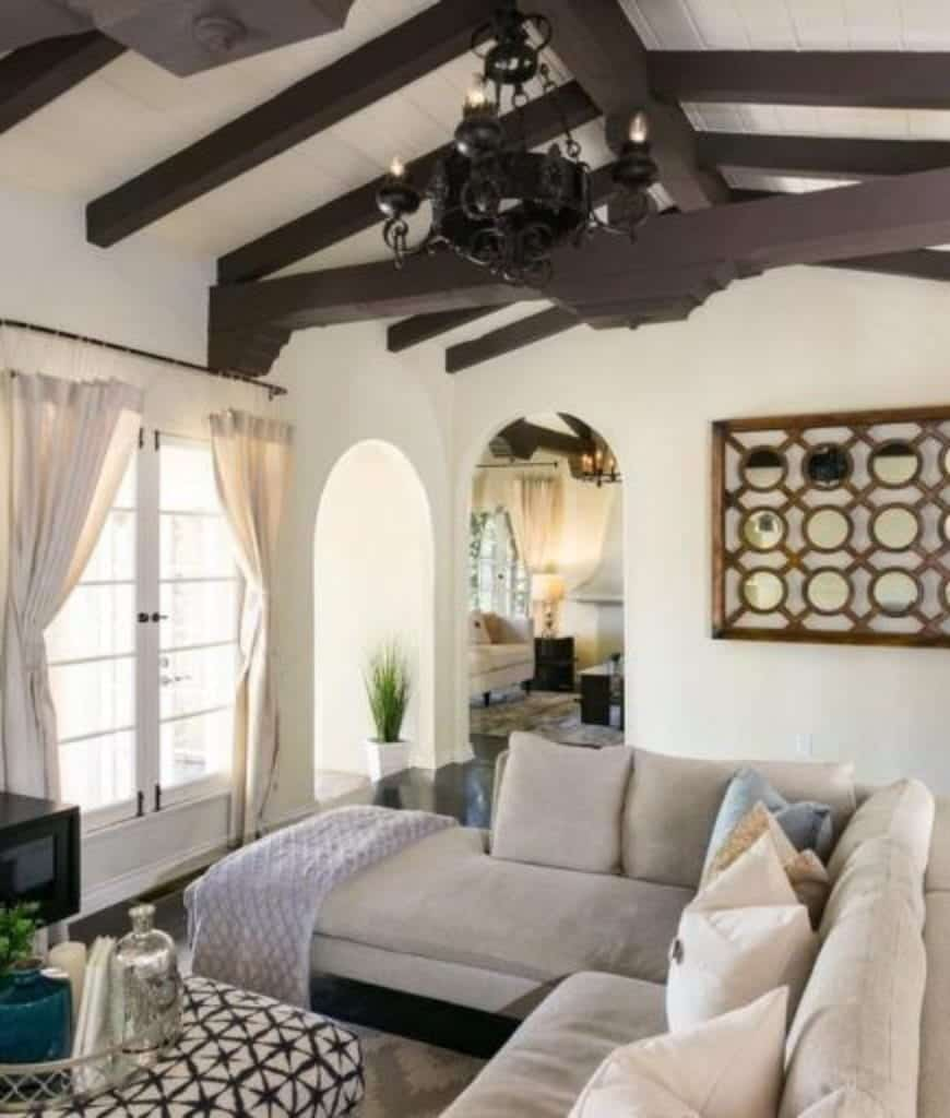 A black chandelier hangs from the wood beam ceiling in this living room decorated with wooden wall art that's mounted next to the open archway.
