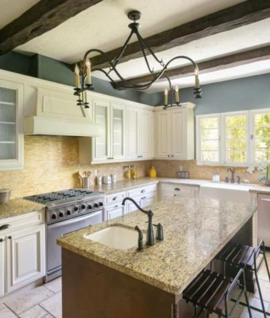 This kitchen is illuminated by a wrought iron chandelier that hung from the wood beam ceiling. It has white cabinetry and a wooden breakfast bar fitted with a sink and black fixtures.