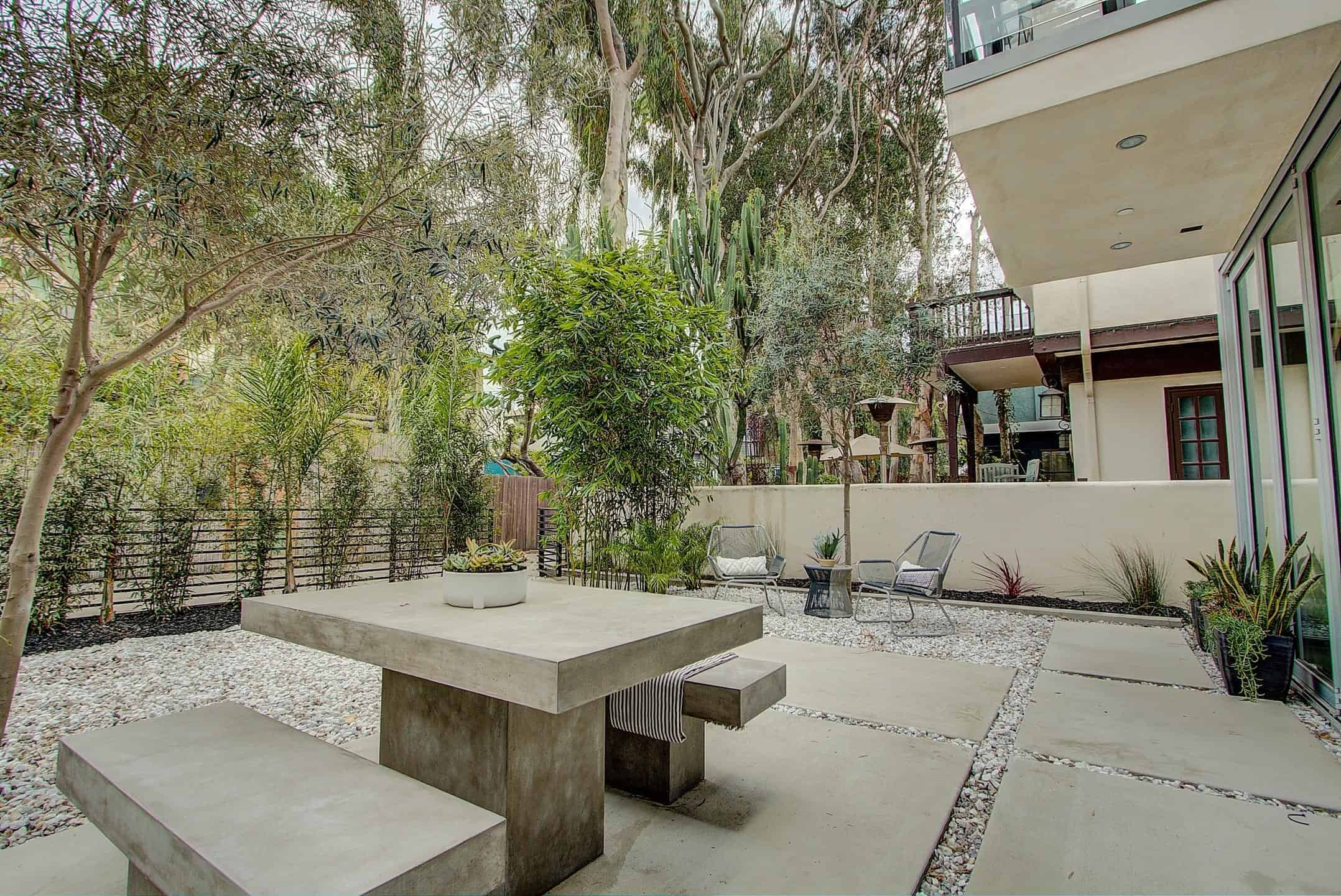 Large outdoor area with stone grounds and concrete walkway. There's a patio area and a dining area made of concrete table and seats. The space is surrounded by many plants and trees.