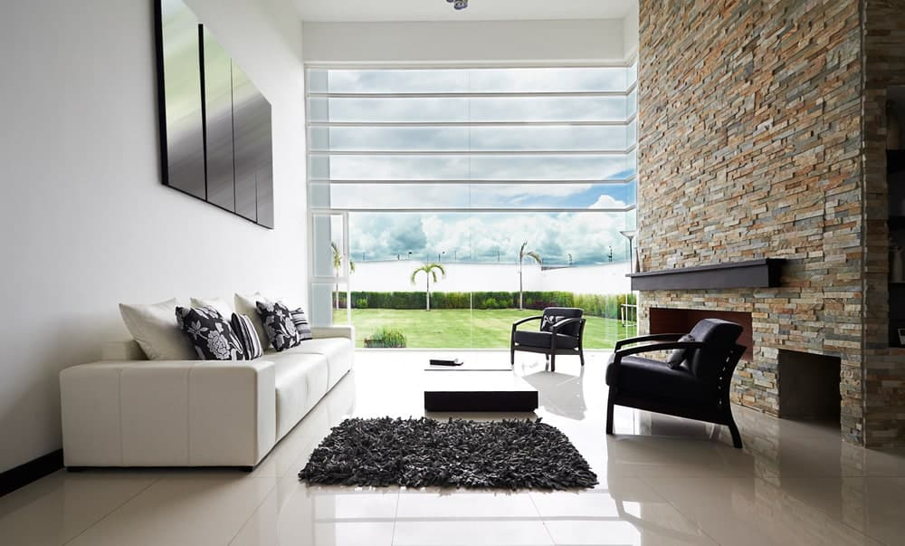 Modern living room interior with white walls opposite a stone brick wall, modern furniture, and white tile flooring.