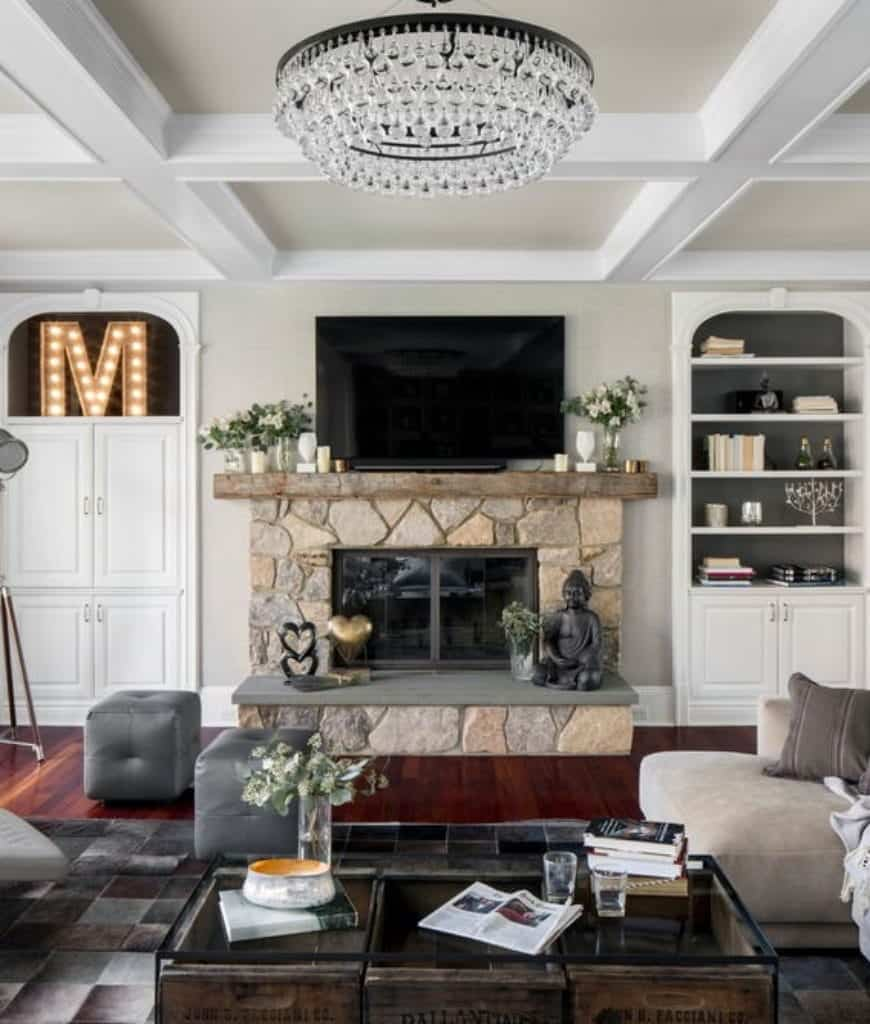 A stone fireplace sits in between built-in cabinets in this living room showcasing a glass top coffee table and a round chandelier that hung from the coffered ceiling.