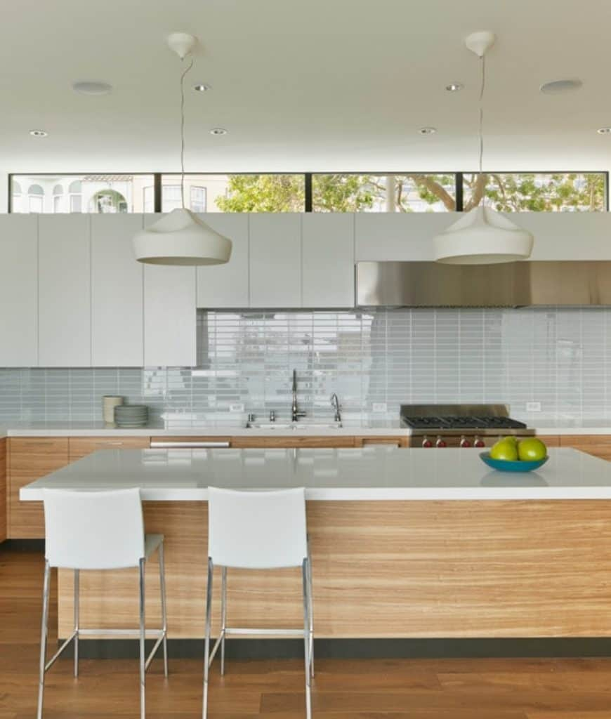 White counter chairs sit at a wooden breakfast bar in this kitchen with white pendant lights and sleek cabinetry accented by high gloss backsplash tiles.