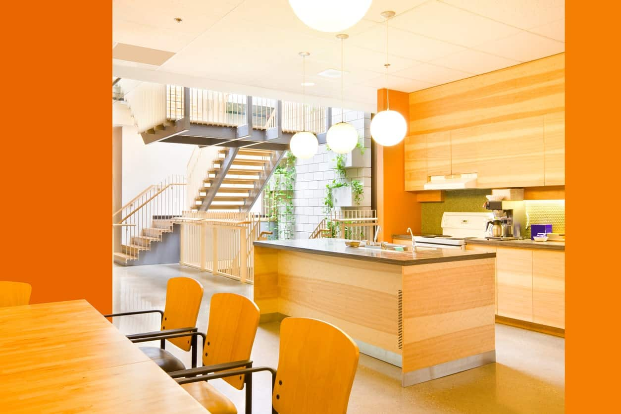 Orange dine-in kitchen featuring a dining table set, a center island and a bright ceiling lighting.