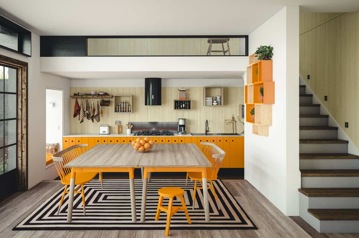 This kitchen features grayish hardwood flooring topped by a rug, where the dining table is set. The orange kitchen counters match the orange chairs and shelving.