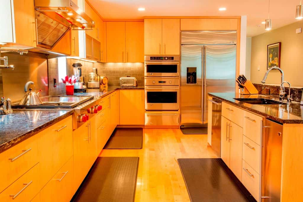 Orange kitchen featuring black granite countertops. The area is lighted by multiple recessed ceiling lights.