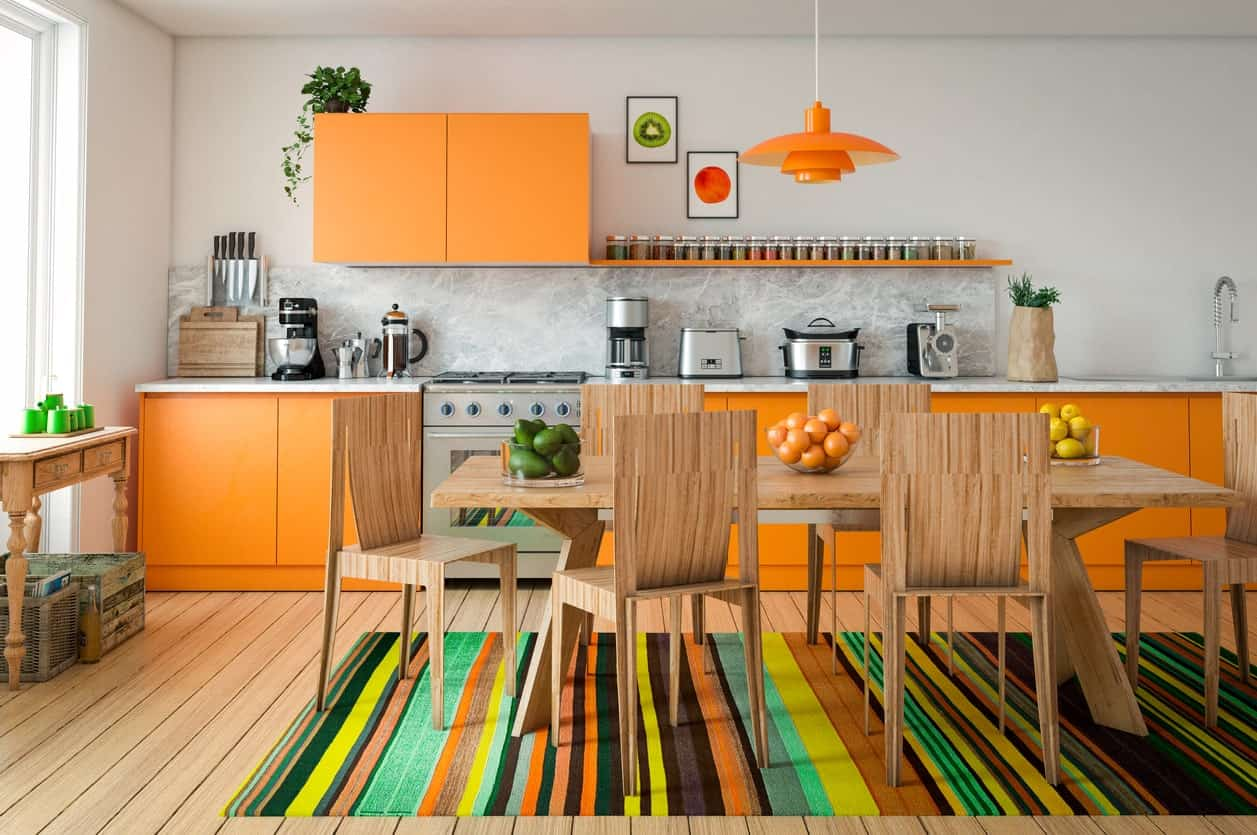 A kitchen featuring hardwood flooring matching the wooden dining table set. The colorful rug looks good together with the room's orange accent.