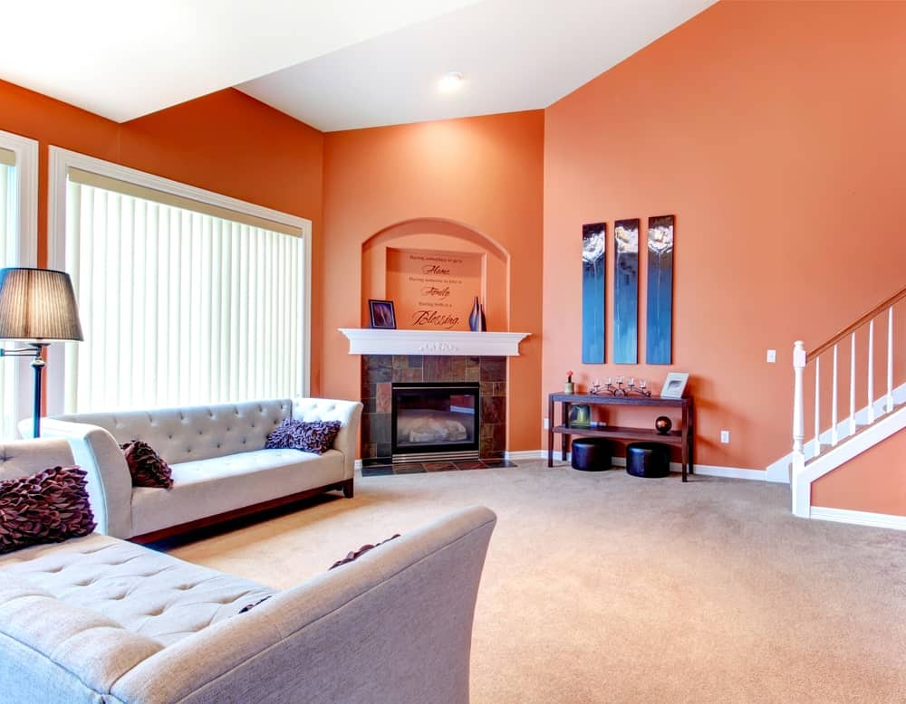 A living room with cozy couches set on the carpet flooring. The room also offers a fireplace. This living room is surrounded by orange walls.