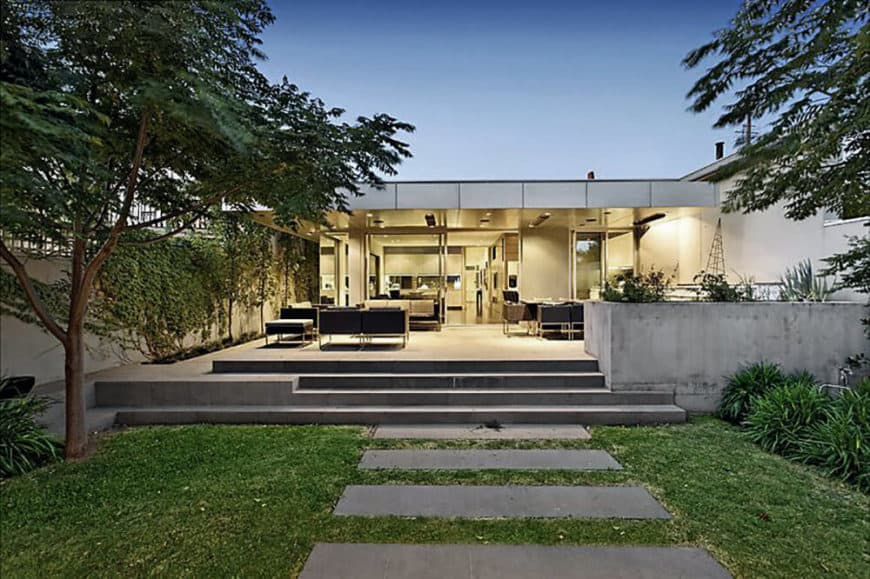 A modern home's backyard featuring a well-maintained lawn area with concrete steps, green plants and mature trees. The home has a large patio area and outdoor dining as well.
