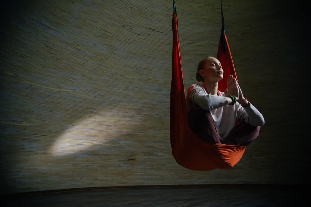 person meditating in suspended meditation chair