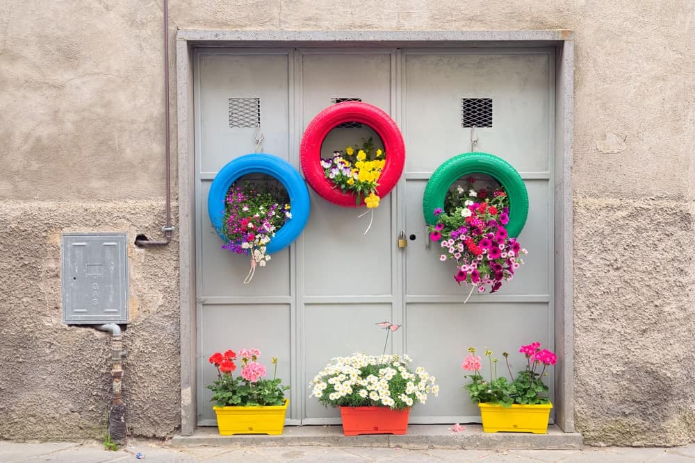 Various colorful planters mounted at a side of a wall.