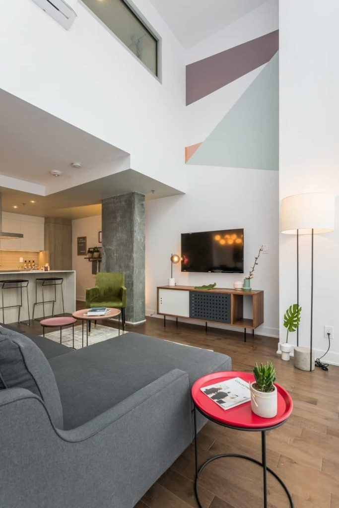 Industrial-style living room with natural hardwood flooring and white walls lined with a concrete pillar. It showcases round metal tables and a gray sofa facing the wall-mount TV that hung above a sleek, wooden stand.