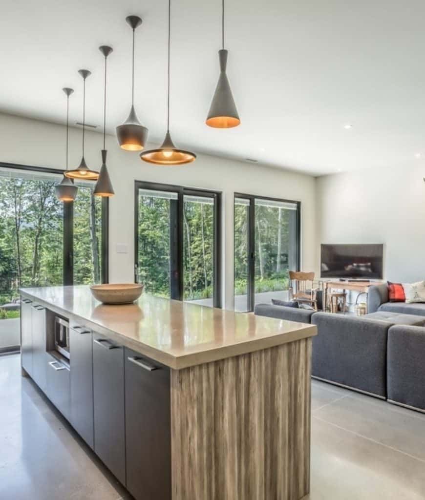 Open concept kitchen with tiled flooring and glass paneled windows overlooking the serene outdoor view. It includes a wooden island bar illuminated by various styled pendant lights.