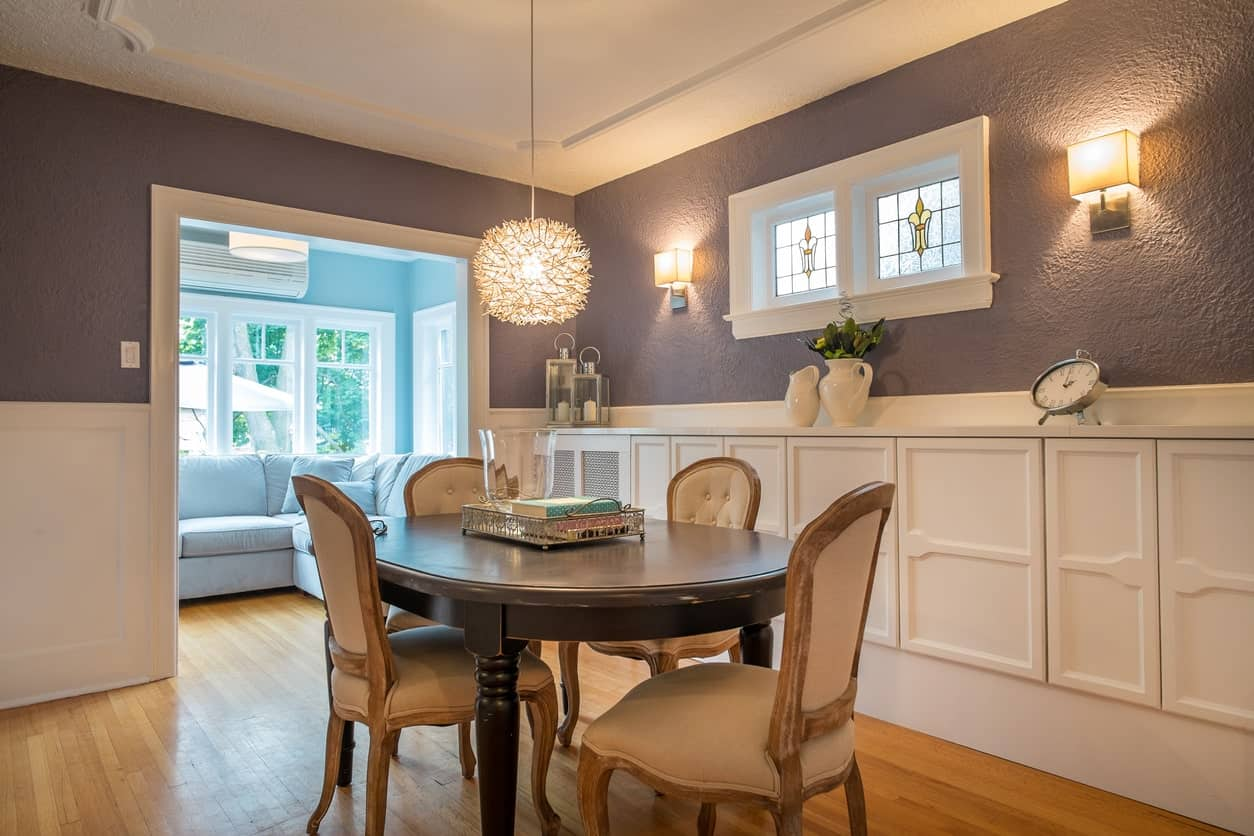 A classy dining room featuring an oval dining table set for four, lighted by a fancy ceiling light. The purple walls are lighted by wall sconces.
