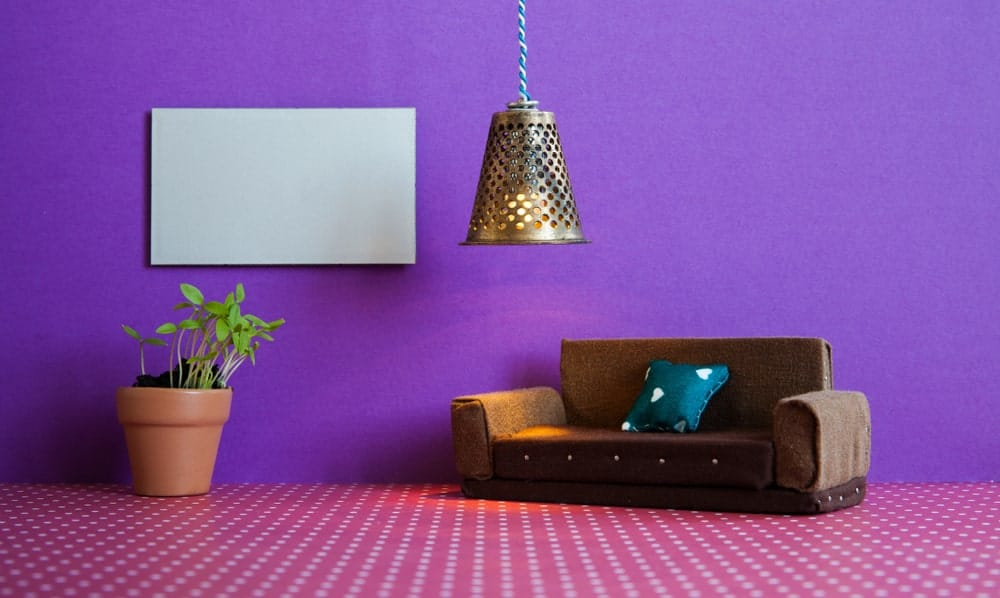 A purple living space featuring deep purple walls and pink flooring with white dots. The brown couch looks good together with the room's style.