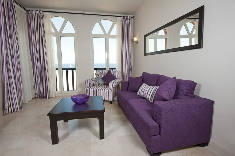 Small living space featuring a purple couch. The room's flooring looks perfect together with the walls and ceiling.