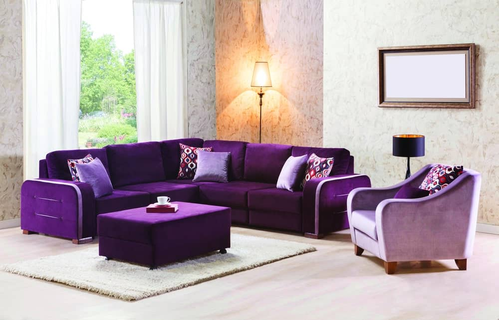 Formal living room boasting an elegant sofa set with a matching ottoman set on a white rug.