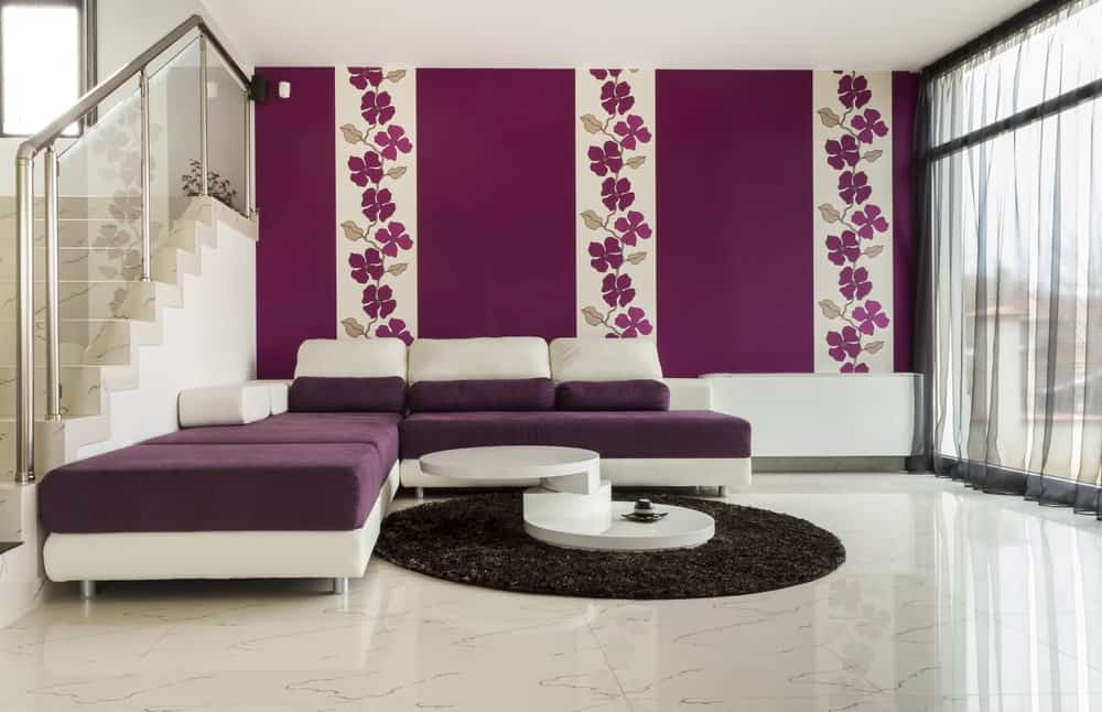Spacious living space featuring a purple accent. The white marble floors topped by a black rug looks classy. The purple wall with lovely floral design looks charming and attractive.