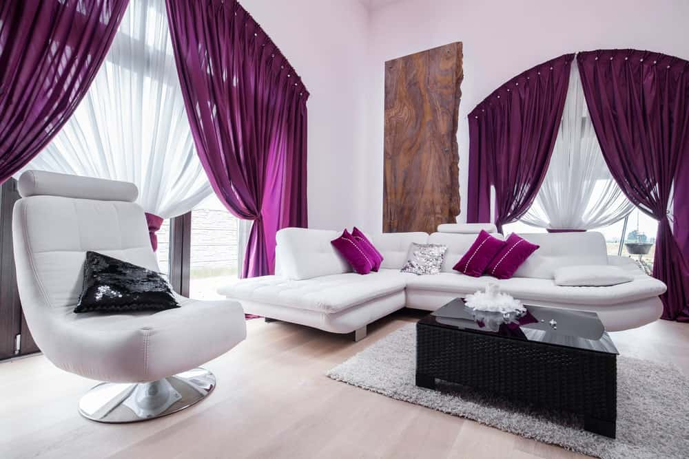 This modish living space features white and purple color schemes. Its purple accent makes the room look sophisticated. The white couch and the modish chair are just classy.