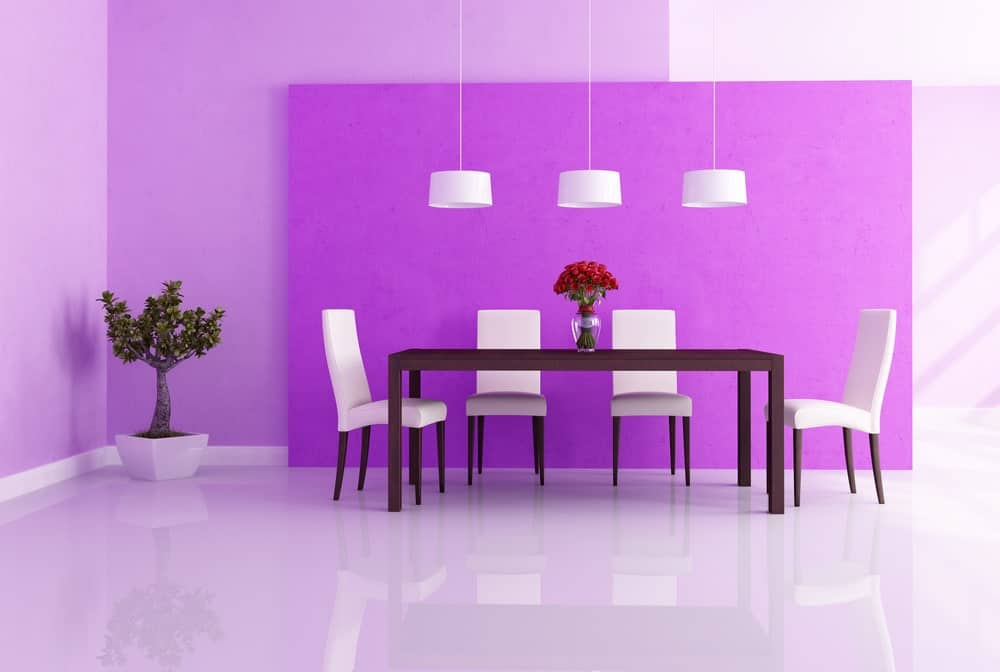 Spacious dining room featuring smooth and shiny white tiles flooring along with rich purple walls. The dining table set is lighted by a set of pendant lights.