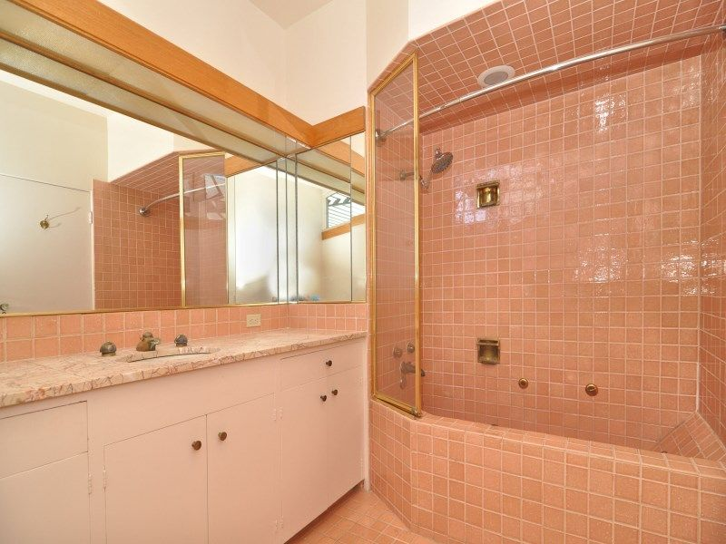 This primary bathroom features orange tiles walls and floors. It has a shower area and its sink boasts a marble countertop.