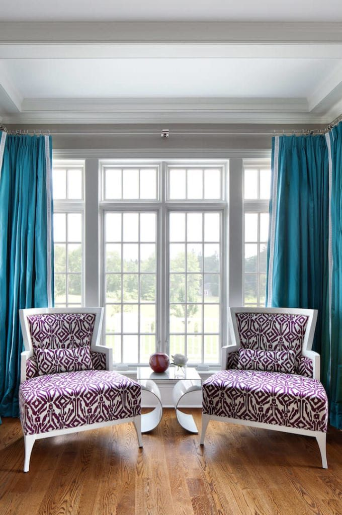 The two purple patterned chairs stand out in this reading nook that is paired with blue curtains of the bright French windows that bring in an abundance of natural lighting that makes the white coffered ceiling shine as well as the hardwood flooring.
