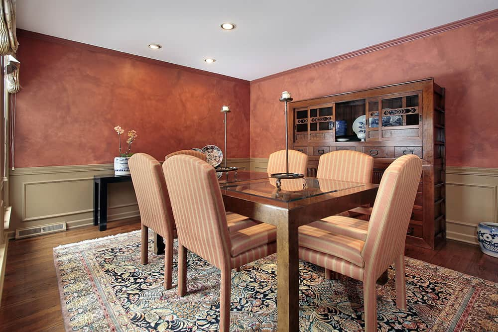 This dining room boasts elegant red walls surrounding the rectangular dining table set on top of the large rug covering the hardwood flooring.