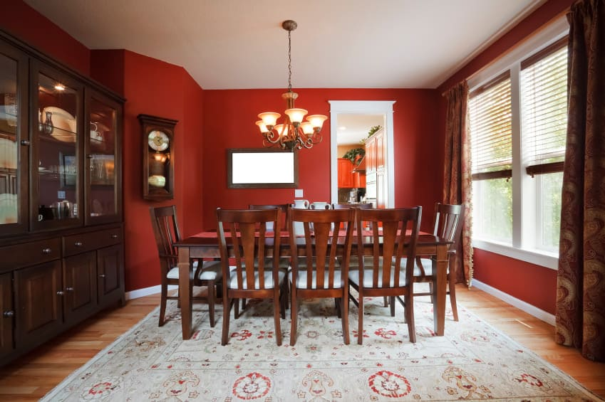 This kitchen offers a wooden dining table and chairs set on top of a rug and is surrounded by rich red walls.