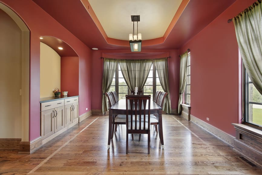 A classy dining area with a tray ceiling, red walls and hardwood flooring. The green window curtains add style to the space.