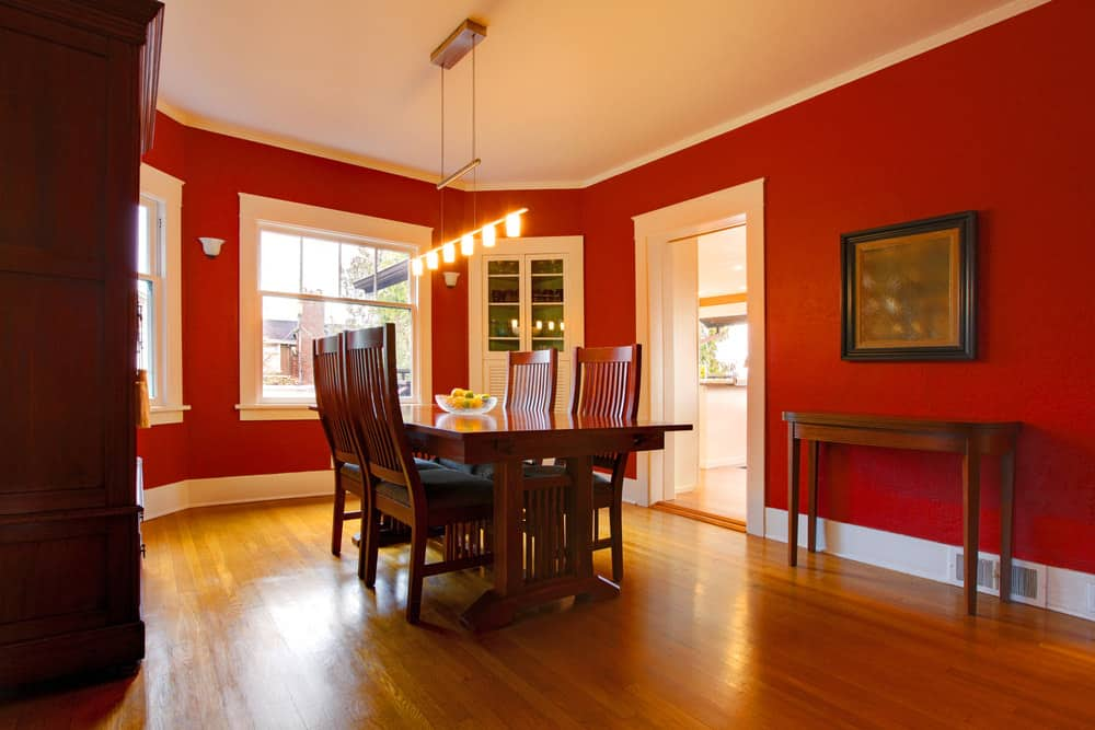 A nicely set dining table and chairs lighted by gorgeous-looking pendant lights, surrounded by rich red walls.