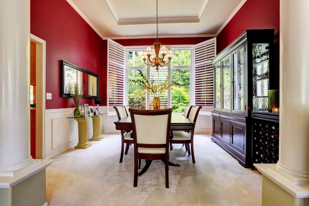 This dining room features rich red walls with a white accent. The classy dining table and chairs set is lighted by a chandelier hanging from the tray ceiling.