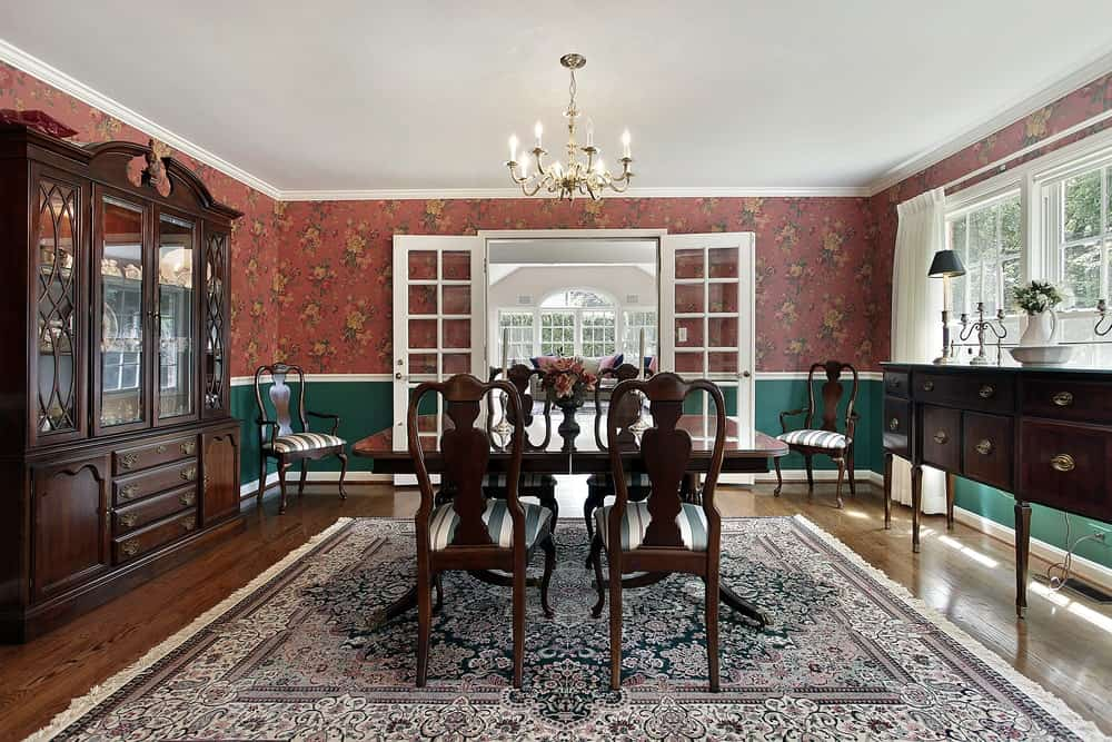 This dining room boasts a square dining table set lighted by a fancy chandelier, surrounded by elegant red walls.
