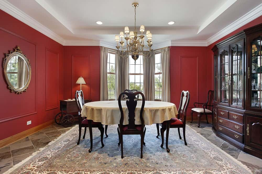 Spacious kitchen featuring classy red walls and gray tiles flooring covered by a large rug. It has a white tray ceiling lighted by a fancy chandelier.