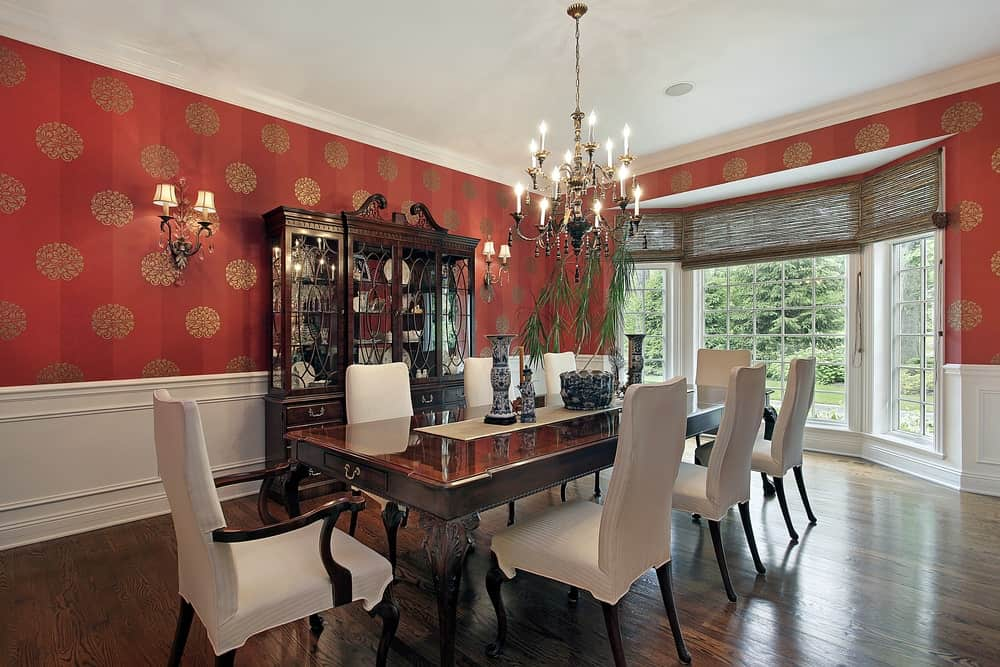 This dining room boasts an elegant dining table and chairs set surrounded by luxurious-looking red walls lighted by a gorgeous chandelier.