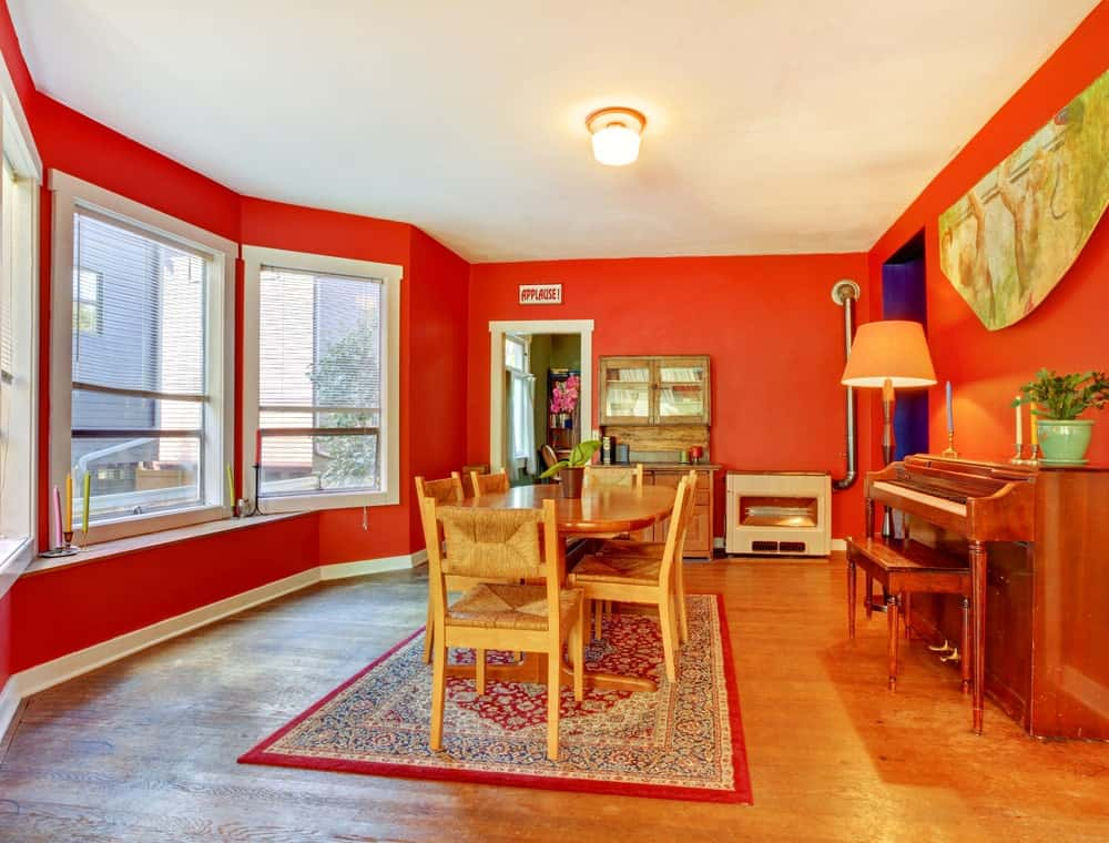 Spacious dining area featuring red walls and hardwood floors. The room has a wooden dining table and chairs set along with a vintage piano on the side.