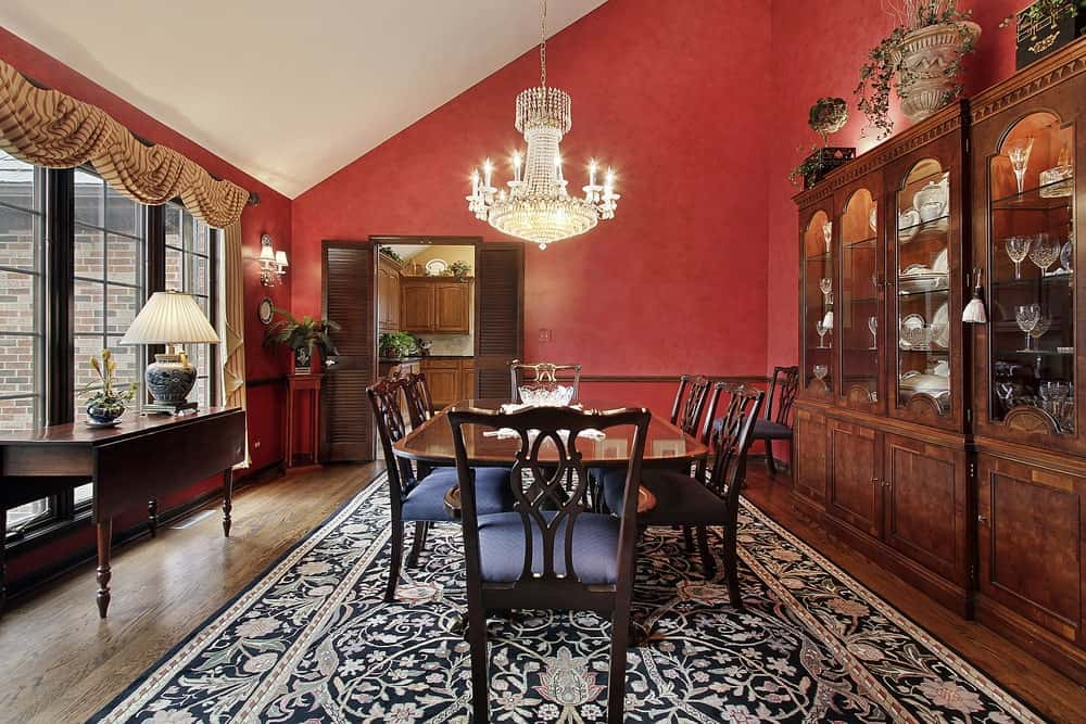 Large dining area featuring a beautiful large rug covering the hardwood flooring. The table and chairs set look classy, surrounded by red walls.