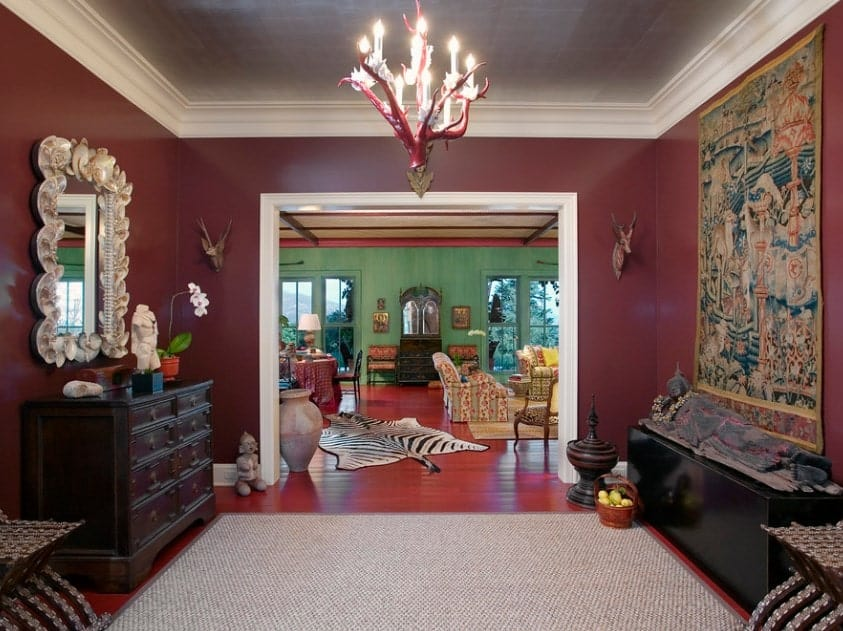 Spacious foyer featuring reddish hardwood flooring topped by a rug, along with dark red walls and a fancy chandelier.