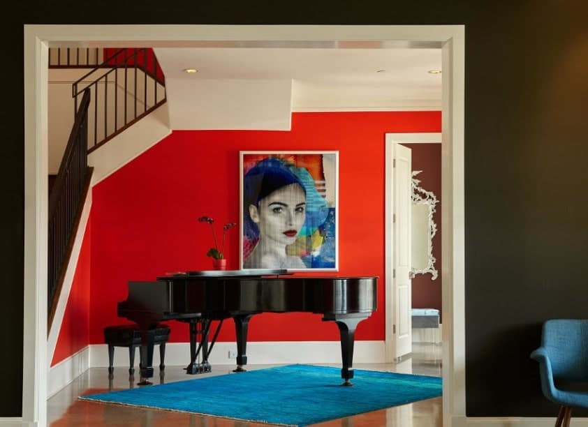 An elegant red foyer with white accent featuring a large artistic portrait wall decor and a black piano.