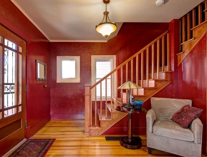 A red foyer and an L-shape staircase lighted by a pendant light with warm lighting.