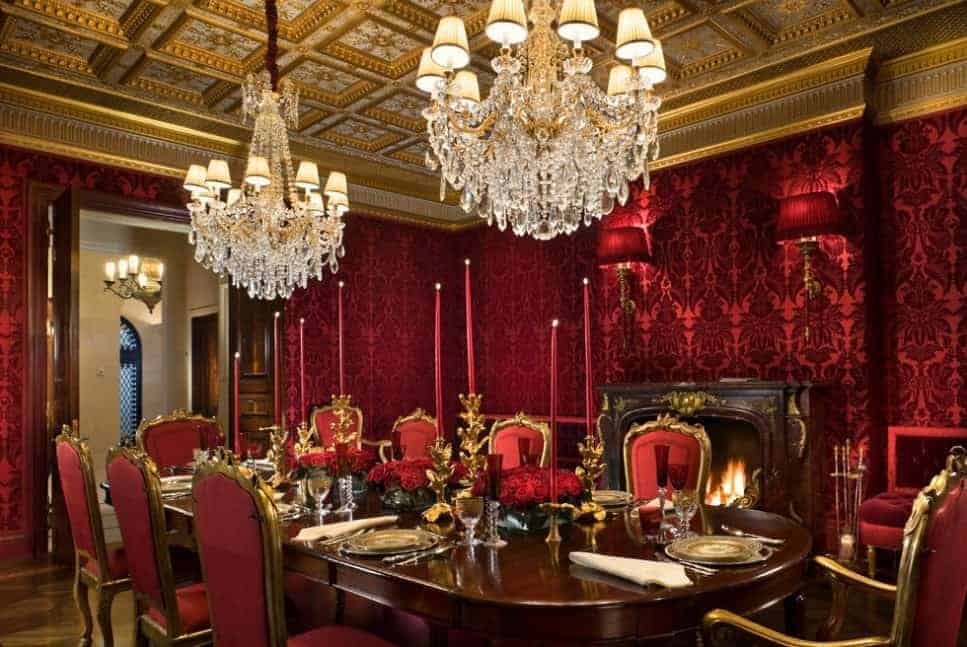 A luxurious dining room covered in elegant red walls with a gold accent lighted by two glamorous chandeliers.