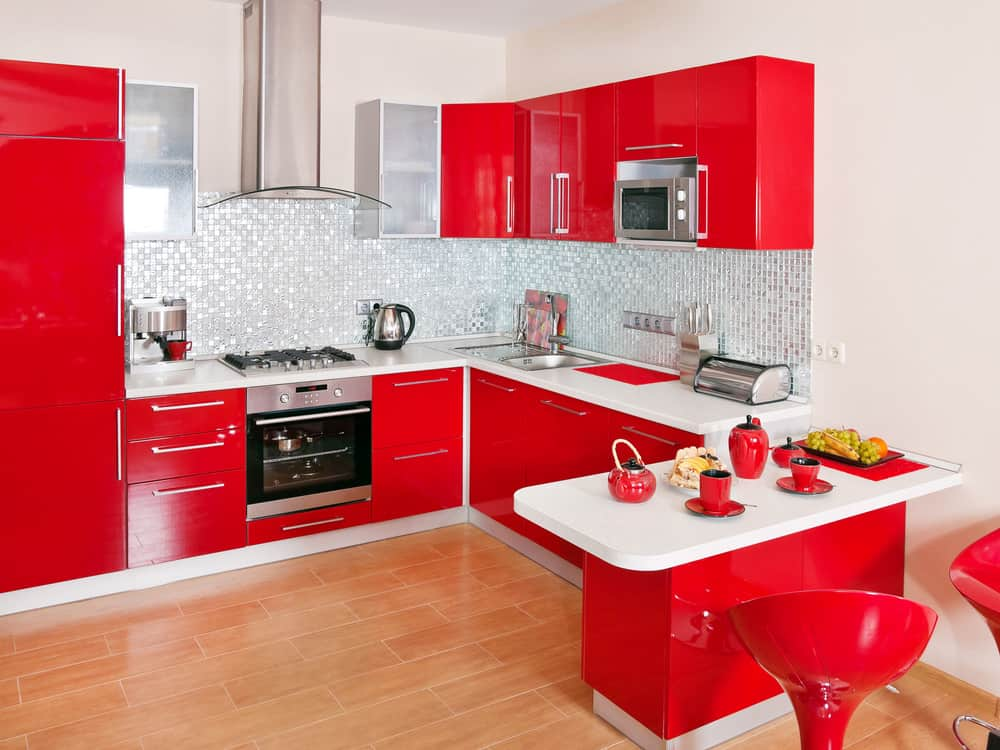 A kitchen with a red accent. It has red kitchen counters, cabinetry and bar stools. The white walls and white countertops look perfect together with the red accent.