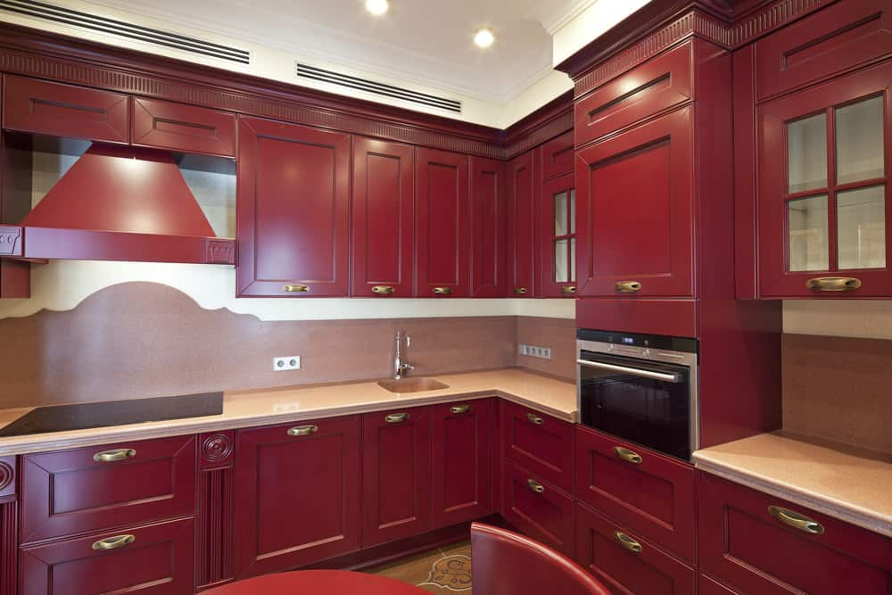 This kitchen features classy red cabinetry and kitchen counters that match the red dining nook.