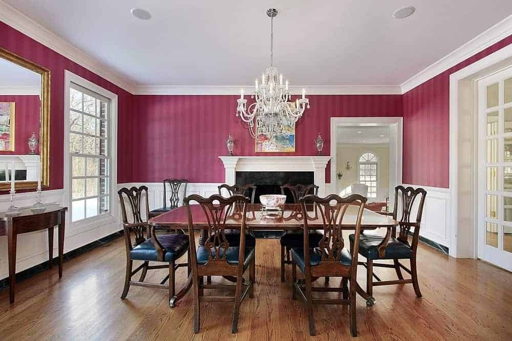 Spacious dining room featuring classy red walls, hardwood flooring and a white regular ceiling lighted by a fancy chandelier. There's a large fireplace on the side as well.