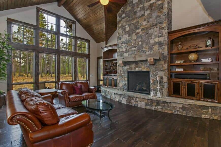 This is an elegant interior with a high cathedral ceiling and leather sofas facing a huge floor-to-ceiling stone structure that houses the fireplace and a pair of wooden shelves on both sides. The massive window on the side gives an ample supply of natural light to the dark wooden flooring.