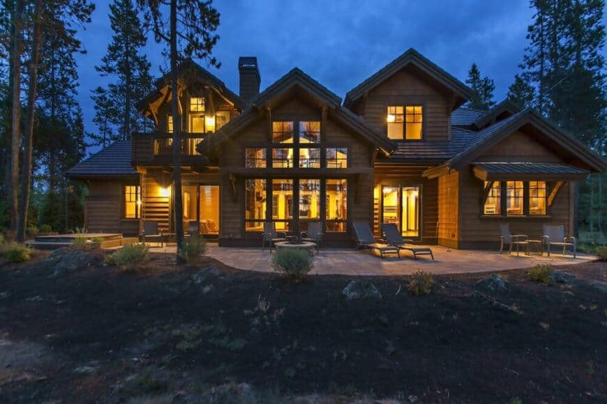 This Craftsman-Style rustic house has a main central section with floor-to-ceiling windows that are provided with a lovely view of the outdoor hearth and landscape. There is a large dormer window at one side of this main section while the other side has a small balcony overlooking the jacuzzi.