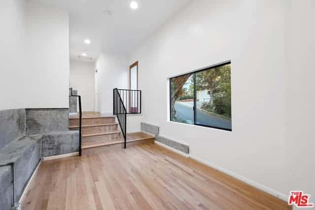 This is a simple and practical foyer design with bare hardwood floors paired with white walls and white ceiling. The guests are given a long stone bench for a waiting area which is built into the sides of the white wall facing a window.