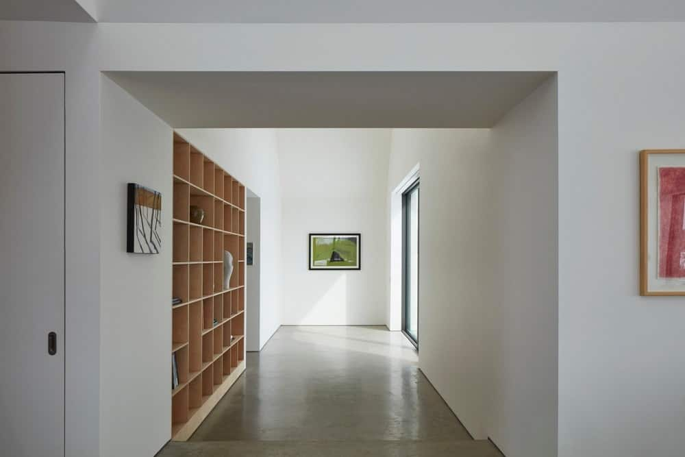 This white-walled Scandinavian-Style foyer has an industrial gray flooring with a high ceiling. The wall by the entrance is adorned by a wall-mounted artwork that stands out against the white walls. There is also a built-in wooden shelf on the adjacent wall.