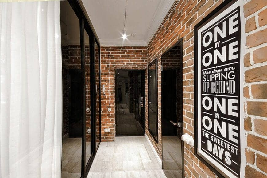 This is a Scandinavian-Style hallway foyer with walls that have a red brick wall finish that makes the sleek black doors pop out against the rough texture. There is a text poster framed and mounted on the wall of the hallway illuminated by the pin lights of the white ceiling.