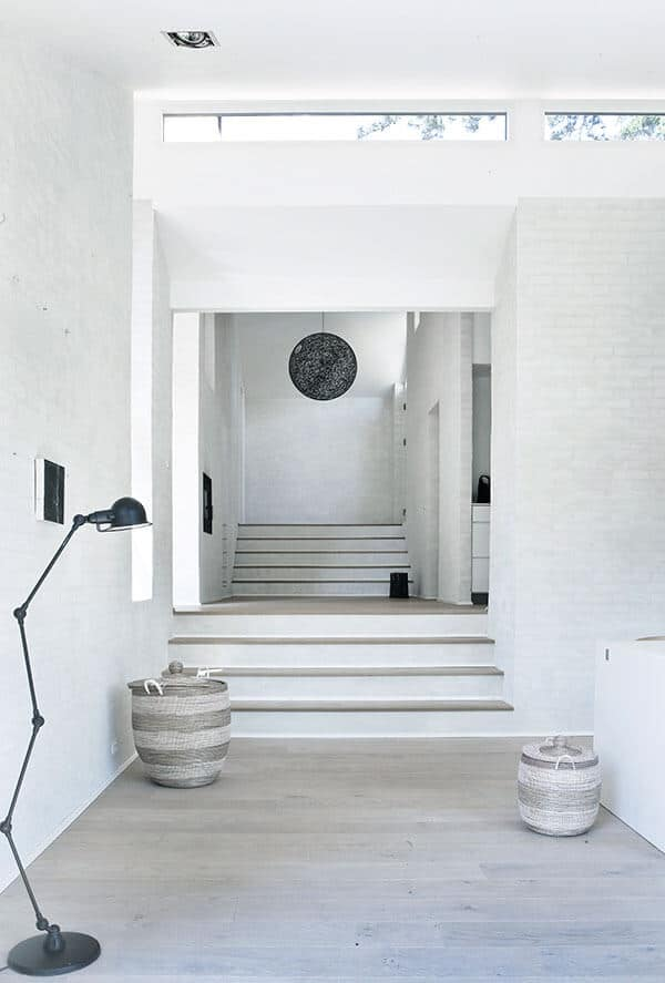 This is a predominantly white Scandinavian-Style foyer with white walls, white ceilings, and hardwood flooring that is bleached white. This is complemented by rustic baskets of the same hue as the floor and contrasted by a black standing lamp and black spherical pendant light.
